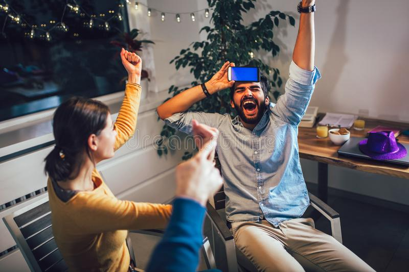 Happy group of friends playing charades at home stock photography