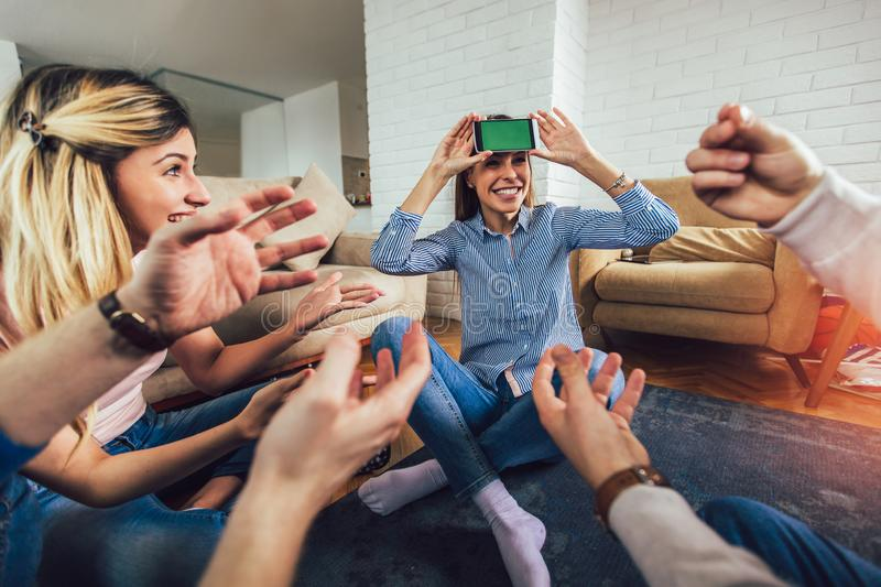 Happy group of friends playing charades at home royalty free stock photography