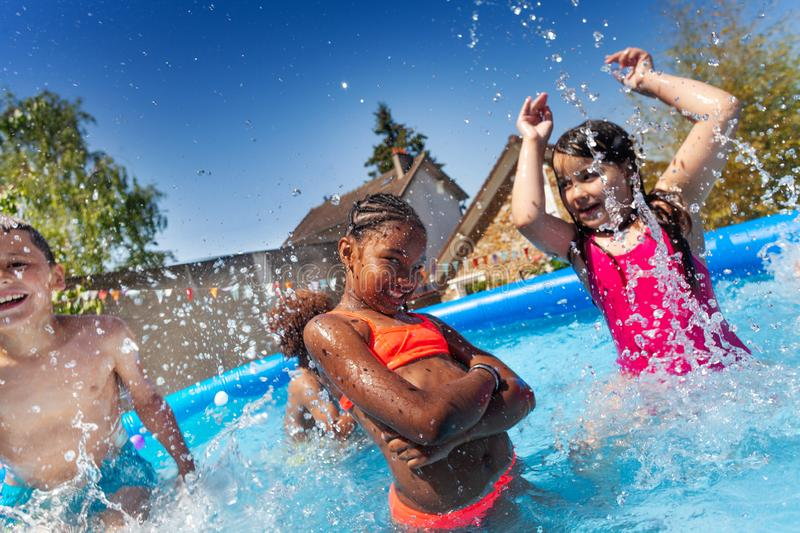 Cute happy girl pose with friends in the pool. Happy group of kids play in inflatable pool with two girls splashing water stock images