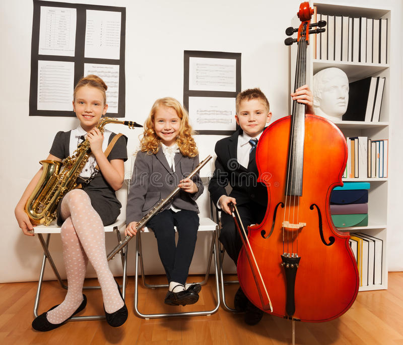 Happy group of kids playing musical instruments. Together while sitting inside musical school stock images