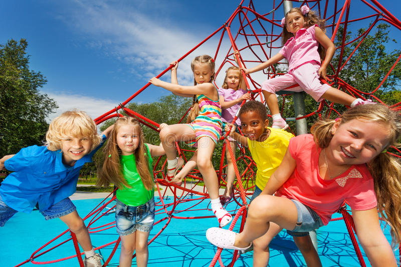 Happy group of kids on red ropes together in park royalty free stock photo
