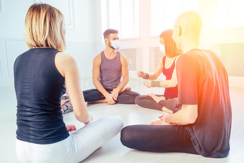 A happy group of men and women practicing yoga in the studio in medical mask. the concept of new lifestyle pandemic royalty free stock images