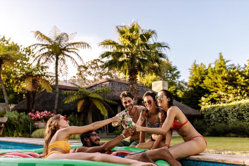 Friends enjoying and toasting beers at pool party. Happy group of men and women in swimming pool drinking beers. Multiracial friends enjoying and toasting beers royalty free stock photography