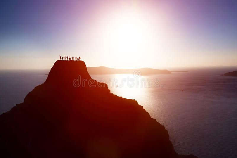 Happy group of people, friends, family on the top of the mountain over ocean celebrating success stock image