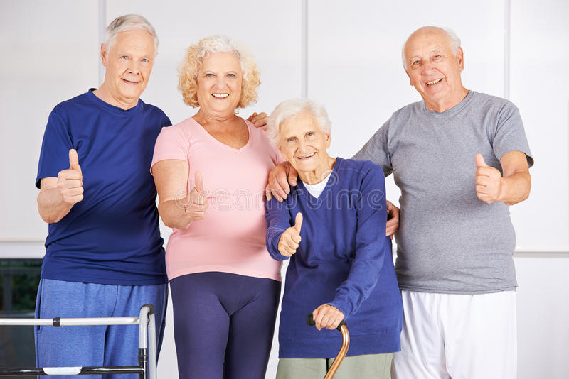 Happy group of seniors holding thumbs up stock images
