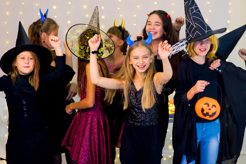 Happy group of teenagers dance in Halloween costumes. During the Halloween party with pumpkins stock image