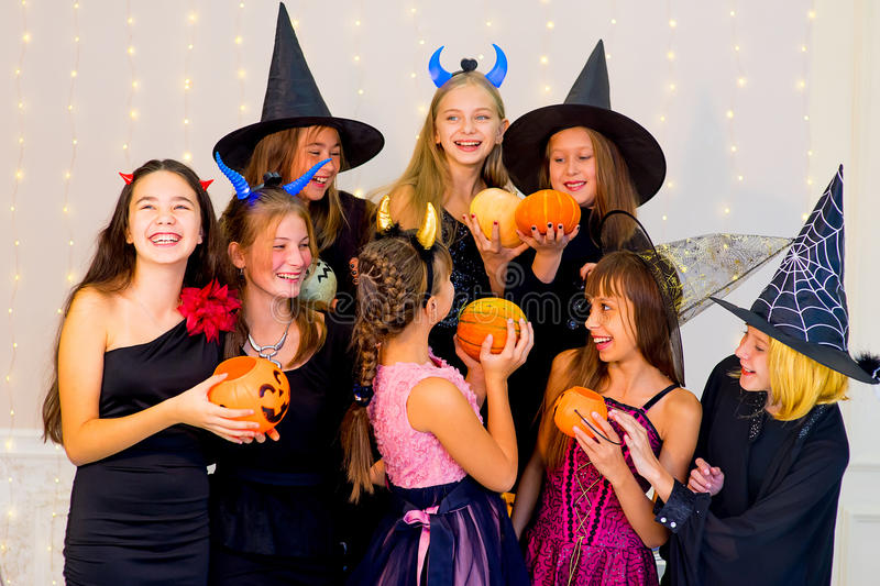 Happy group of teenagers in Halloween costumes posing on camera. With pumpkins, smiling and joking royalty free stock photo