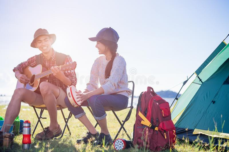 Happy group young friends in camping tent party having playing m. Usic fun together on outdoor holiday summer stock image