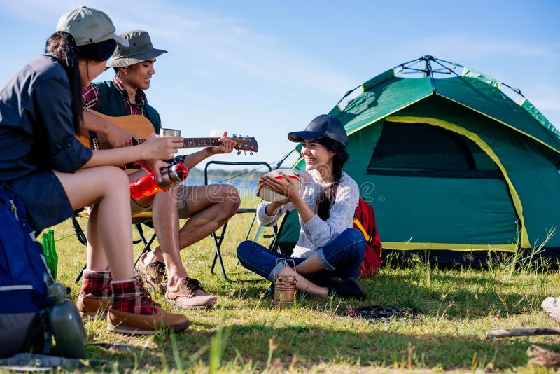 Happy group young friends in camping tent party having playing m. Usic fun together on outdoor holiday summer stock photography