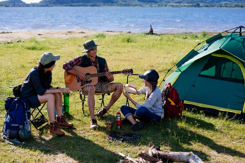 Happy group young friends in camping tent party having playing m. Usic fun together on outdoor holiday summer stock photos
