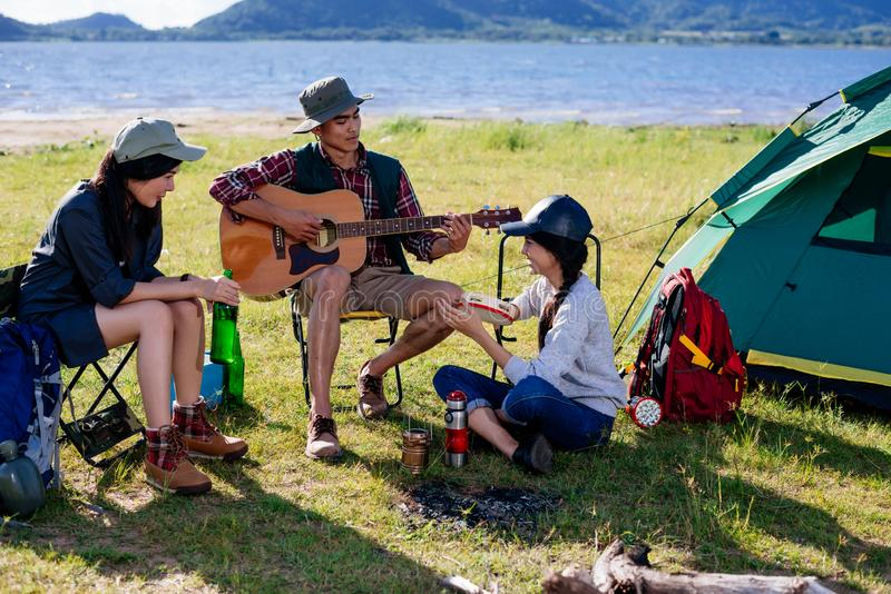 Happy group young friends in camping tent party having playing m. Usic fun together on outdoor holiday summer royalty free stock photo