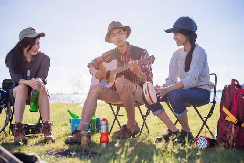 Happy group young friends in camping tent party having playing m. Usic fun together on outdoor holiday summer stock images