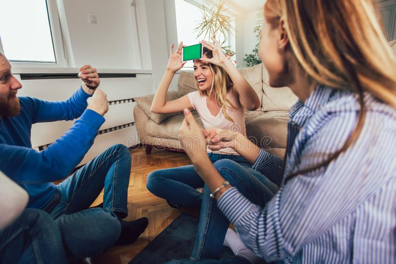 Happy group of friends playing charades at home stock photos