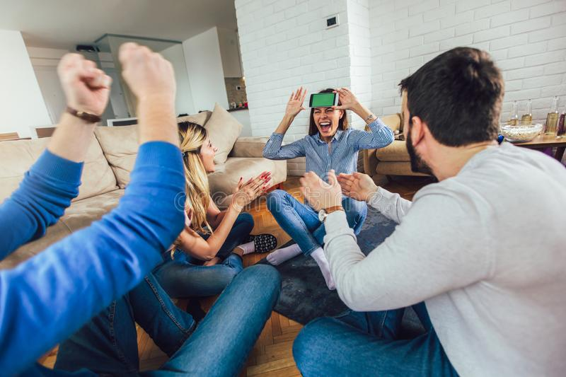 Happy group of young friends playing charades at home stock photos