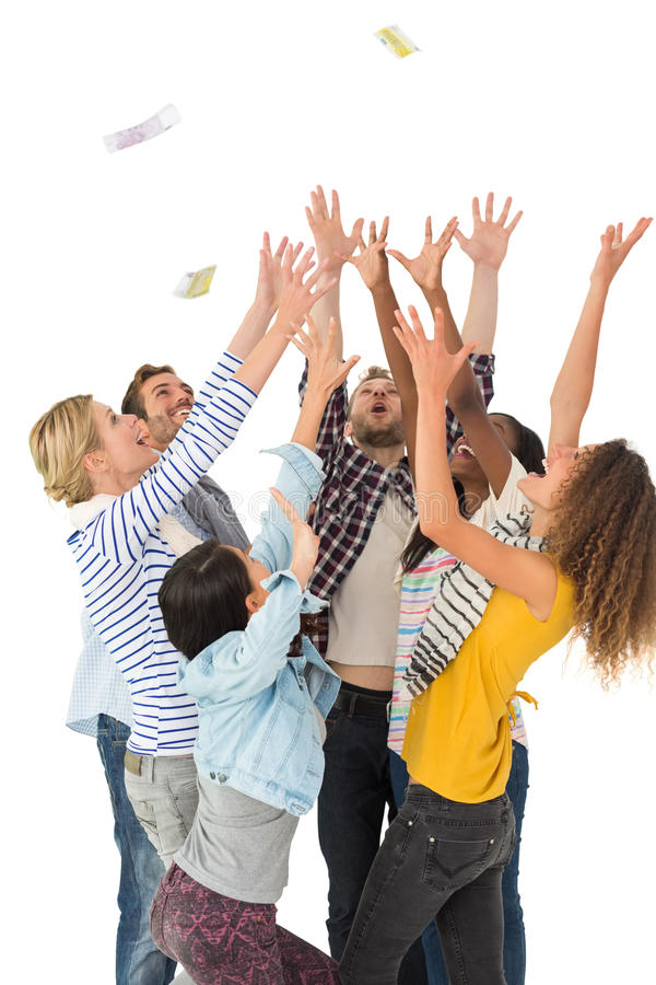 Happy group of young friends throwing money in the air stock photography