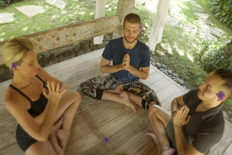 Happy group of young hipster American friends enjoying Asian yoga retreat together sitting on lotus position meditating at stock images
