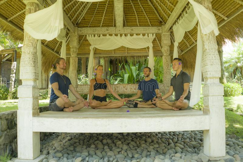 Happy group of young hipster American friends enjoying Asian yoga retreat together sitting on lotus position meditating at royalty free stock photo