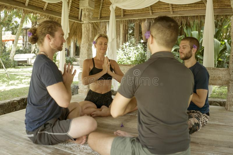 Happy group of young hipster American friends enjoying Asian yoga retreat together sitting on lotus position meditating at royalty free stock photos