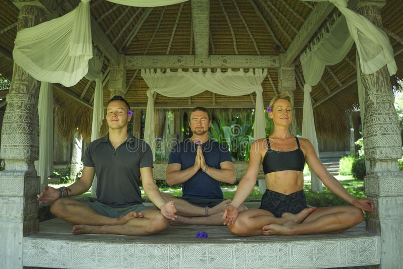 Happy group of young hipster American friends enjoying Asian yoga retreat together sitting on lotus position meditating at royalty free stock photography