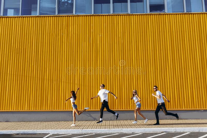 Happy group of young people having fun while running and jumping in the city royalty free stock images