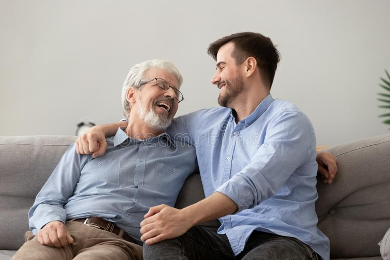 Happy grown son sit on couch talk with senior dad. Smiling grown son sit on couch relax with senior dad talk sharing thoughts looking in eyes, happy millennial royalty free stock image
