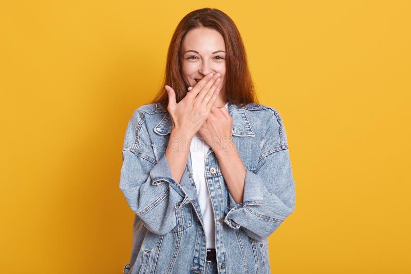 Happy gut aussehendes junges Modell, das ihren Mund mit beiden Händen bedeckt, schüchtern überrascht aussehen, in hohen Geistern, lizenzfreie stockfotografie