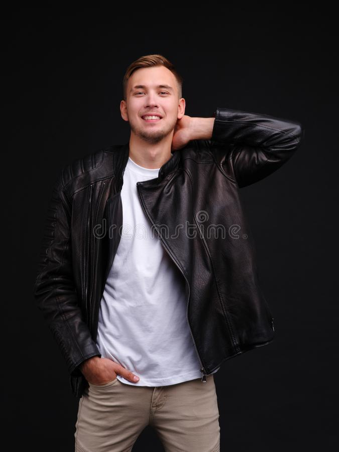 A happy guy in a black jacket holds to neck with a smile. royalty free stock photography