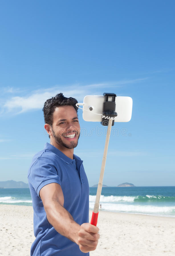 Happy guy with blue shirt and beard at beach taking selfie with stick. With ocean and blue sky in the background stock images