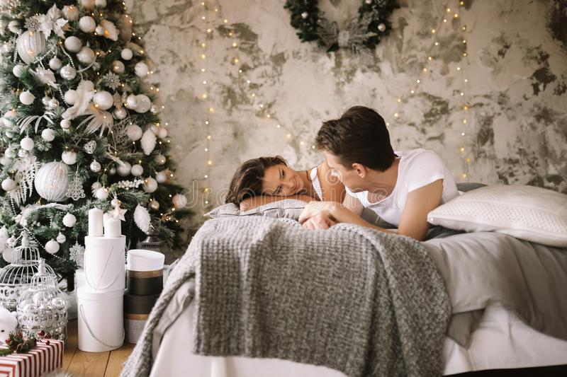 Happy guy and girl dressed in white t-shirts are lying on a bed and looking at each other.  stock image