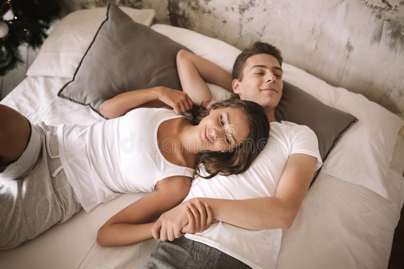 Happy guy and girl dressed in white t-shirts are lying on a bed with a white blanket with gray pillows and holding hands.  stock image