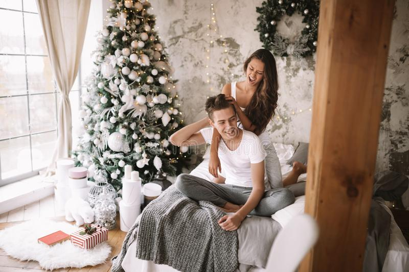 Happy guy and girl dressed in white t-shirts are sitting and hugging on the bed with a gray blanket in a cozy decorated. Happy guy and girl dressed in white t stock photography
