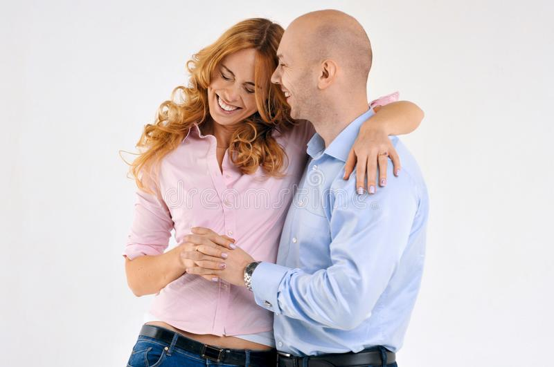 Happy guy and girl. Girl is hugging the boy. Beautiful happy couple. stock photos