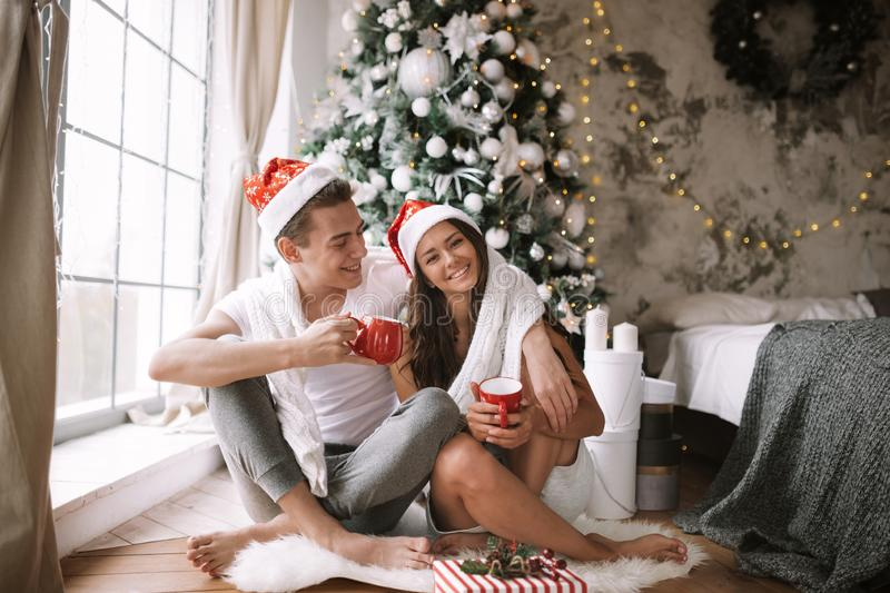 Happy guy and girl in white t-shirts and Santa Claus hats sit with red cups on the floor in front of the window next to. The New Year tree, gifts and candles royalty free stock photos