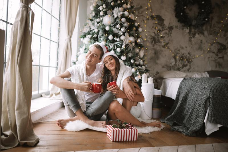 Happy guy and girl in white t-shirts and Santa Claus hats sit with red cups on the floor in front of the window next to. The New Year tree, gifts and candles stock photos