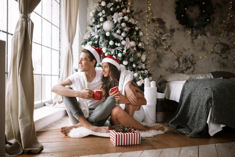 Happy guy and girl in white t-shirts and Santa Claus hats sit with red cups on the floor in front of the window next to. The New Year tree, gifts and candles royalty free stock photography