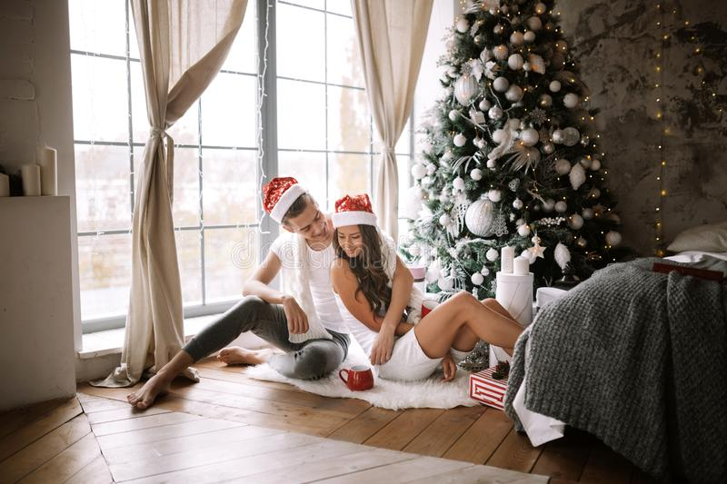 Happy guy and girl in white t-shirts and Santa Claus hats are sitting and hugging in the room on the floor in front of. The window next to the New Year tree royalty free stock image