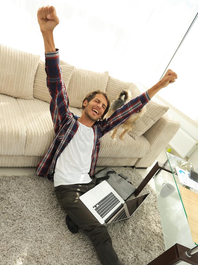 Happy guy with laptop jubilant in spacious living room. royalty free stock photos