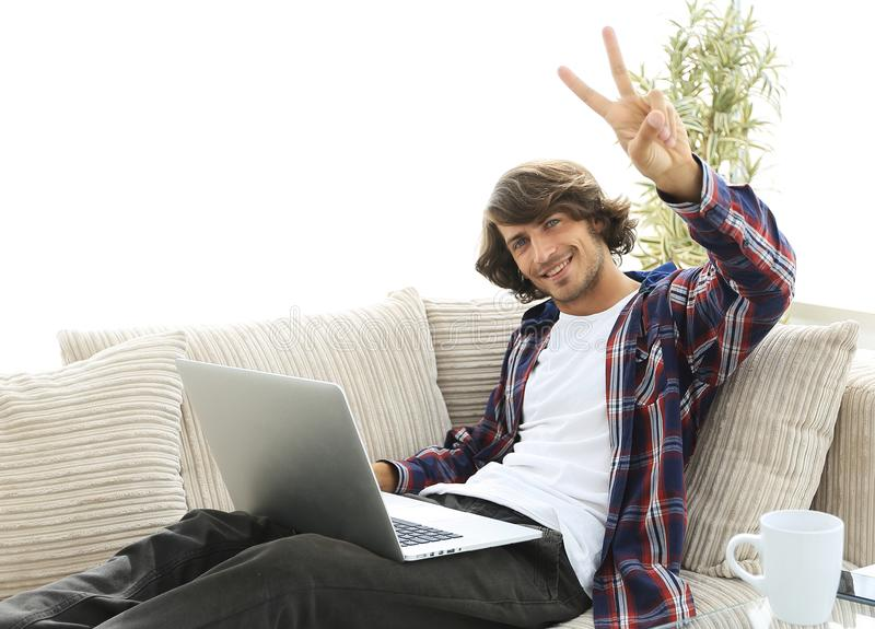Happy guy with laptop sitting on sofa and showing his hand a winning gesture. Guy with laptop sitting on sofa and showing hand winning triumph. concept of a stock photo