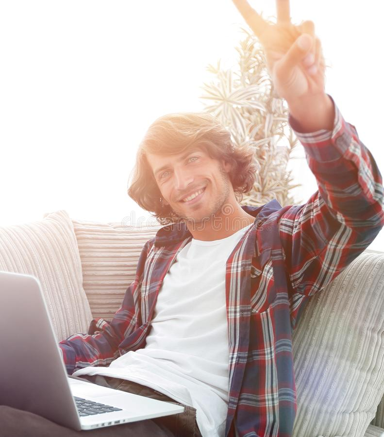 Happy guy with laptop sitting on sofa and showing his hand a winning gesture. Guy with laptop sitting on sofa and showing hand winning triumph. concept of a stock image
