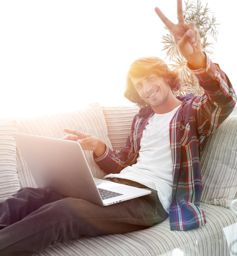 Happy guy with laptop sitting on sofa and showing his hand a winning gesture. Guy with laptop sitting on sofa and showing hand winning triumph. concept of a stock photos