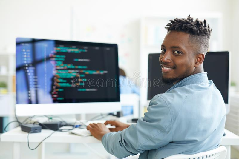 Testing software. Happy guy looking at you while sitting by workplace and working with software royalty free stock photos
