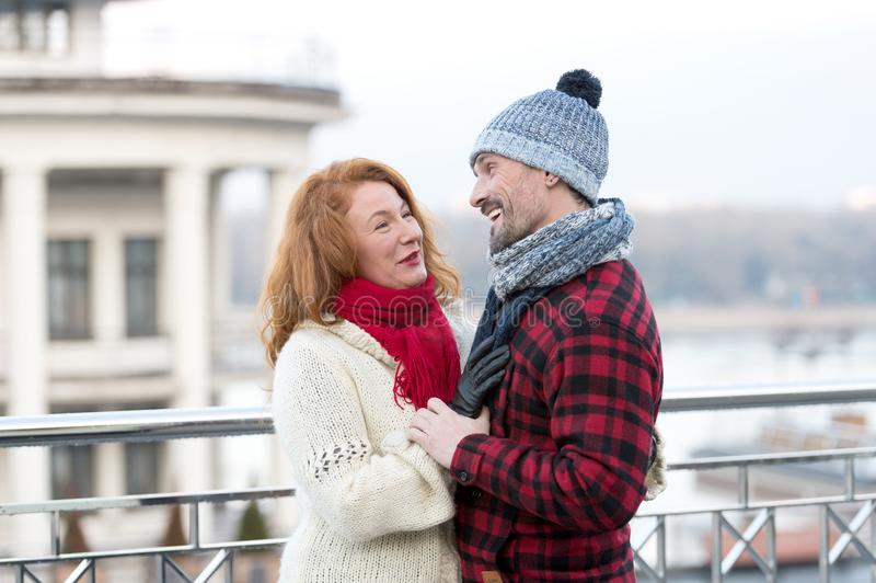 Happy guy looks to woman. Urban couple date on bridge. Red hair woman meet smiling guy. woman and laughing men on city background royalty free stock image