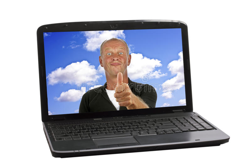 Happy guy showing thumbs up. In screen of a laptop royalty free stock image