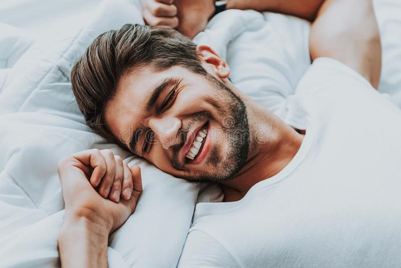 Happy guy stretching in bed in morning royalty free stock image