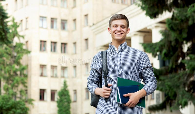 Happy guy student waiting for lessons near university outdoor stock photos