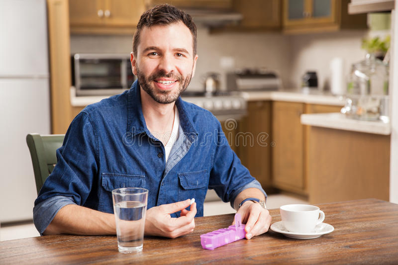 Happy guy taking his vitamins. Portrait of a good looking happy Hispanic man taking his vitamins in the morning at home royalty free stock photos