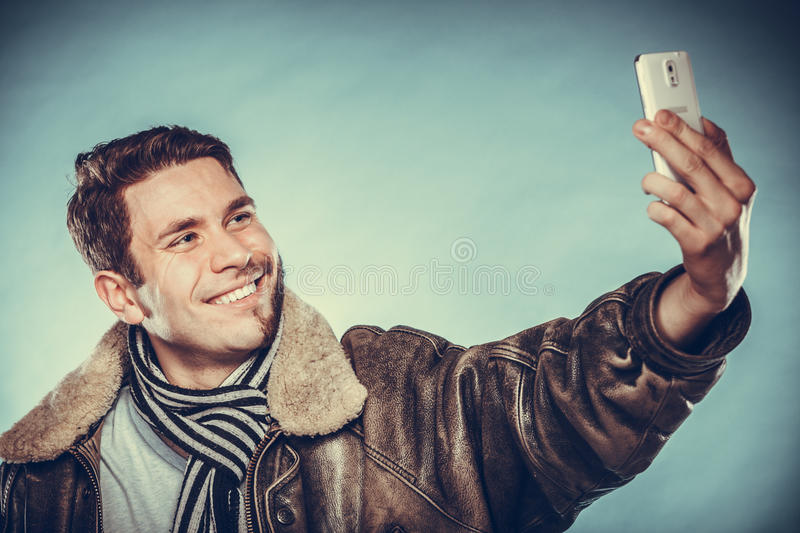 Happy half shaved man taking selfie self photo. Happy man with half shaved face beard hair taking selfie self photo with smartphone camera. Smiling handsome guy royalty free stock image