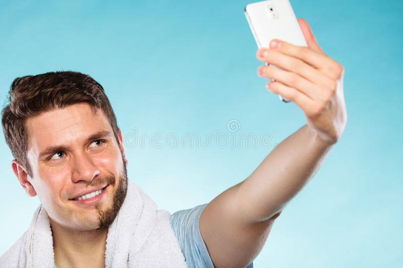 Happy half shaved man taking selfie self photo. Happy handsome man with half shaved face taking selfie self photo with smartphone camera stock images