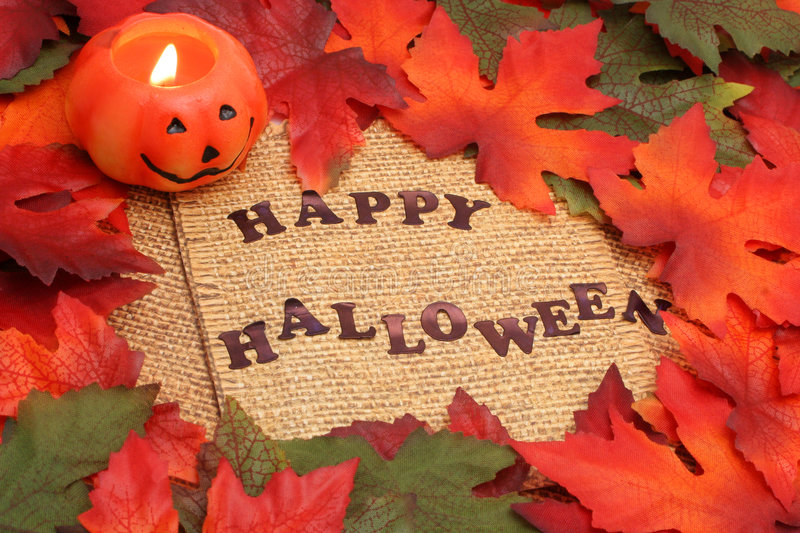 Happy halloween. Background with green and oranges leaves covering twin rope paper and lit jack-o-lantern stock image