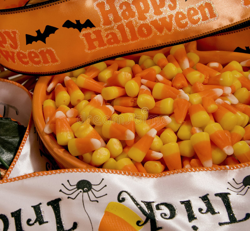 Happy Halloween. Halloween candy corn in a jack-o-lantern bowl with seasonal banners royalty free stock images